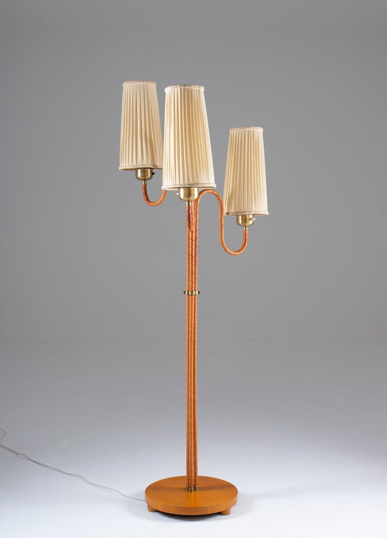 Rare floor lamp manufactured in Sweden, 1930-40s.  This floor lamp consists of three leather webbed bases, connected by a brass divider and a wooden foot. Each base holds a light source, hidden by off-white fabric shades.  Condition: Good vintage