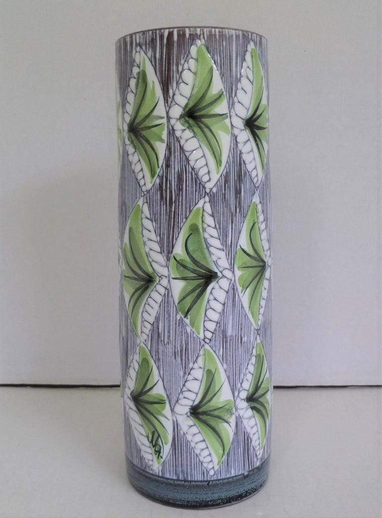 Lovely 1960s cylindrical Swedish modern ceramic vase from the Laholm pottery with hand painted plants/leaves in lime green on a sgrafitto design over the white underglaze. The carved pattern creates the soft textured feel of the vase while the