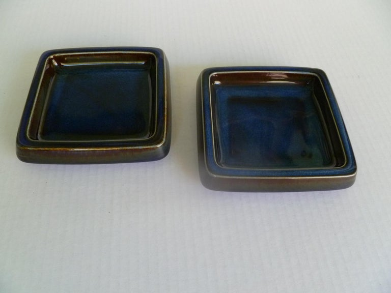 A pair of Swedish Mid-Century Modern shallow Lagun 3 stoneware vessels by Sven Jonson for Gustavsberg, 1970s. Heavy stoneware catch-all bowls or ashtrays, glazed in a thick rich blue glaze with earthen overtones. Incised on bottom with Gustavsberg