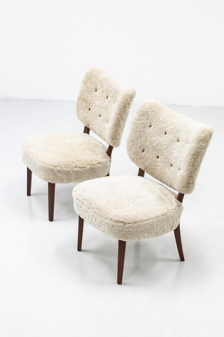 Pair of Swedish modern lounge chairs. Reminiscent to the style of Otto Schulz. Made in Sweden during the 1940-50s. Stained beech wood and new sheep skin fur upholstery with cognac leather buttons. Very good vintage condition. Upholstery is new.