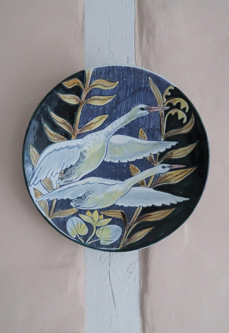 Stunning handmade item by Swedish Tilgmans Keramik. Fully glazed hanging wall decoration depicting two white swans in flight and long stemmed plants on a striped dark blue background created with the sgraffito technique. Manufactured in 1957 by