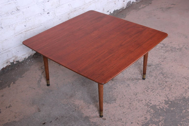 Offering a gorgeous Mid-Century Modern Swedish coffee table attributed to Folke Ohlsson for DUX. The table features beautiful walnut wood grain and sleek Scandinavian design. The table rests on four tall solid walnut brass-tipped pencil legs. Marked