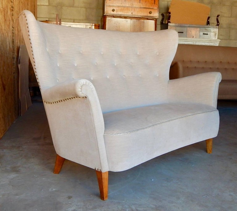 Swedish moderne winged back sofa, circa 1940. In excellent original condition with some stains on original off-white velvet. Solid birch frame. Legs in stained birchwood.
