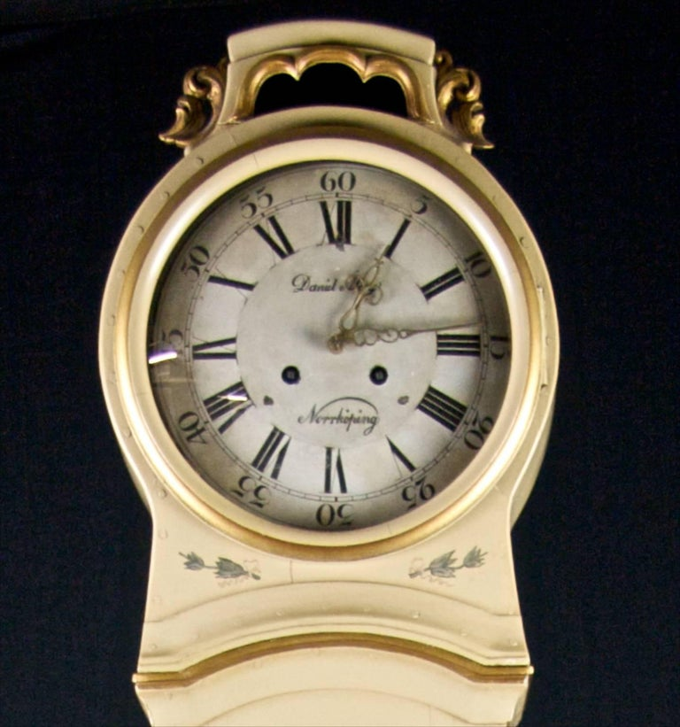 Early 1800s Mora clock with stunning handpainted trompe l'oeil flower wreathes and patterns with sumptuous carved detail on the hood and plinth.