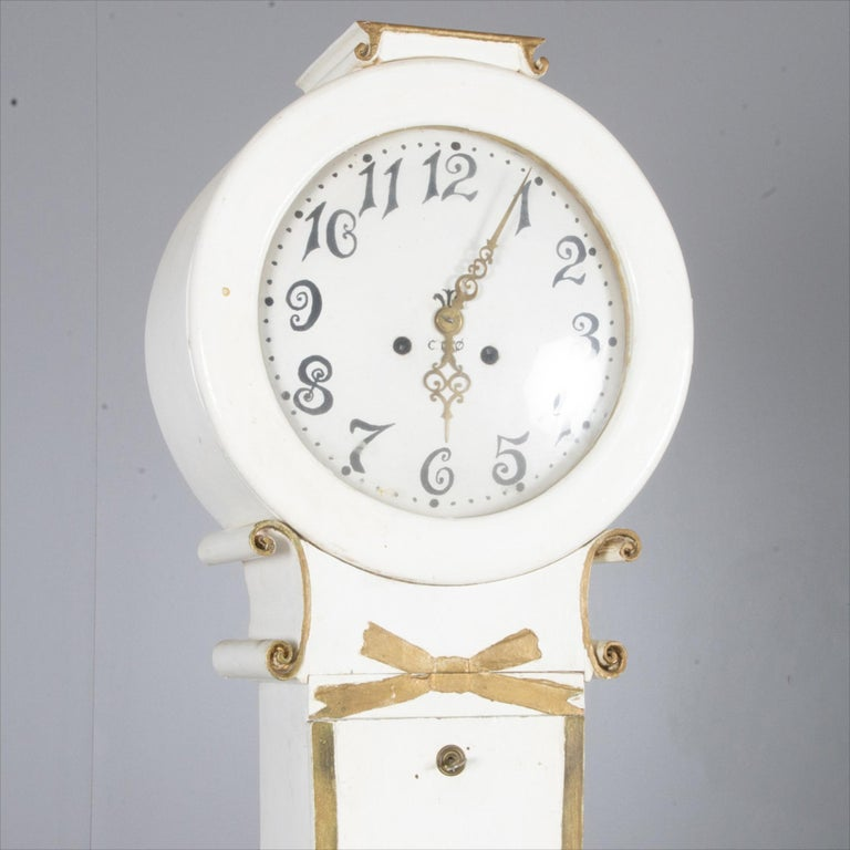 Swedish antique Mora clock in the Fryksdall school finished in White paint with gold edge detailing.