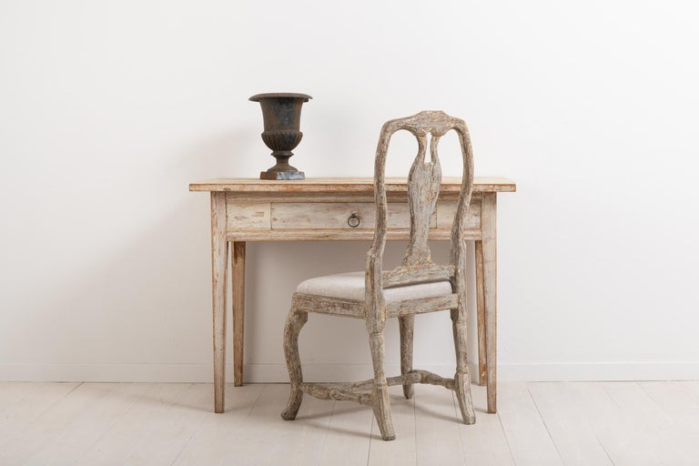 Neoclassic desk from northern Sweden. The desk is from circa the turn of the century 1700-1800. The light paint is original and naturally worn after years of use. Straight tapered legs typical to the neoclassic and Gustavian eras. One centered