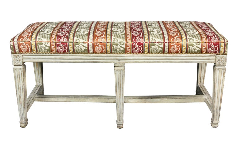With rectangular upholstered seat over a frame with six tapered legs headed by paterae, joined by stretchers.