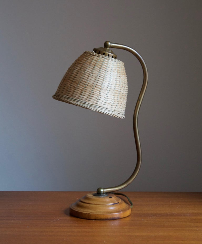 A table lamp, designed and produced in Sweden, circa 1930s. Features an organic brass rod on a wooden base. Assorted vintage rattan lampshade.