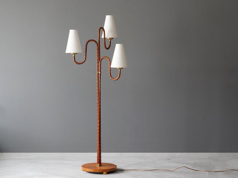 An organic three-armed floor lamp. Designed by an unknown Swedish modernist designer, 1930s. Possibly manufactured by Böhlmarks. Produced in rattan, wood, linen, and brass. Arms adjustable.   Other designers working in the organic style include Jean
