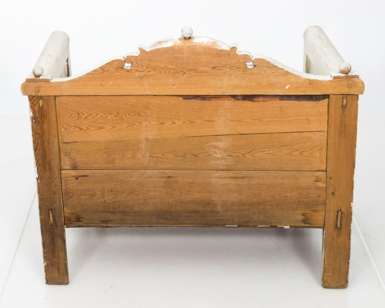 Swedish white painted bench with arms, a curved top rail, and bottom storage underneath seat, circa 1900.