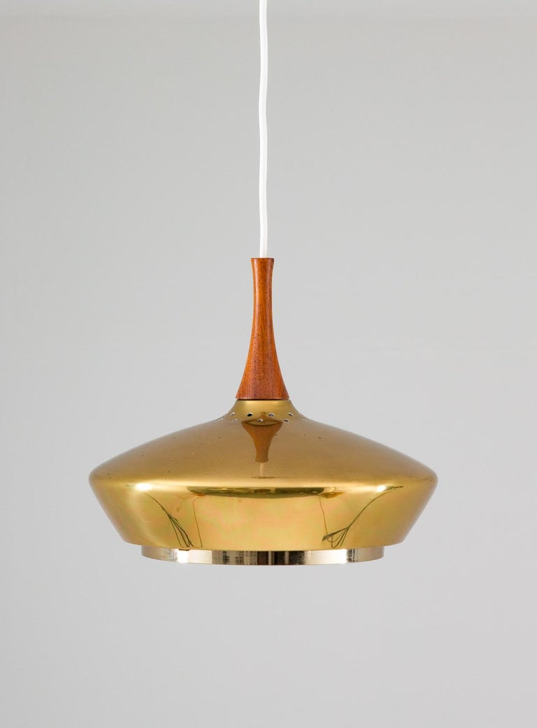 Rare ceiling lamp in brass and wood manufactured by Fagerhult, Sweden. The lamp is made of thick brass and comes with its original brass canopy. The beautiful shape reminds a lot of model