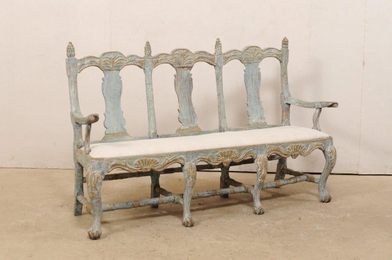 A Swedish period Baroque three-chair back carved-wood sofa, with upholstered seat, from the 18th century. This fabulous hand carved wood bench features three carved back splats for resting, flanked within wood arm rests at each far end. The top rail
