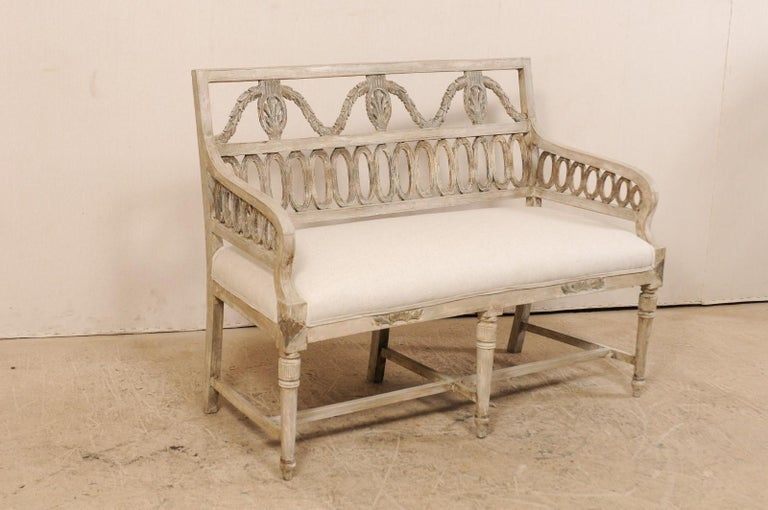 A Swedish period late Gustavian sofa bench with upholstered seat form the early 19th century. This antique sofa bench from Sweden has beautiful carved pierced splat backs in an oval-ring and garland motif. The sofa has a flat top rail along back,