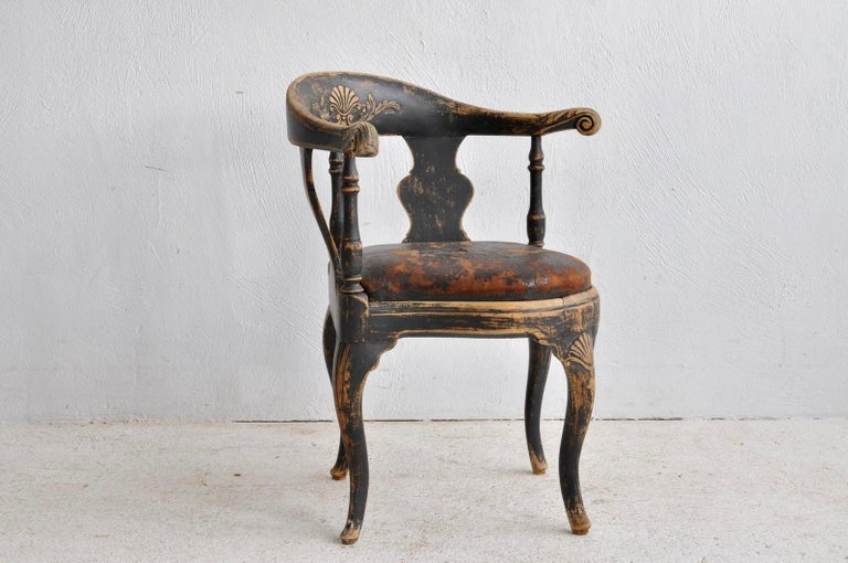 A period Swedish Rococo corner chair, black painted and with an old leather seat.