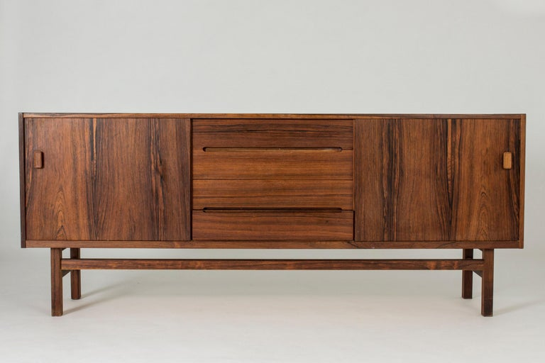 Cool rosewood sideboard by Nils Jonsson. Beautifully sculpted handles in the drawers in the middle and veneer laid in contrasting directions.