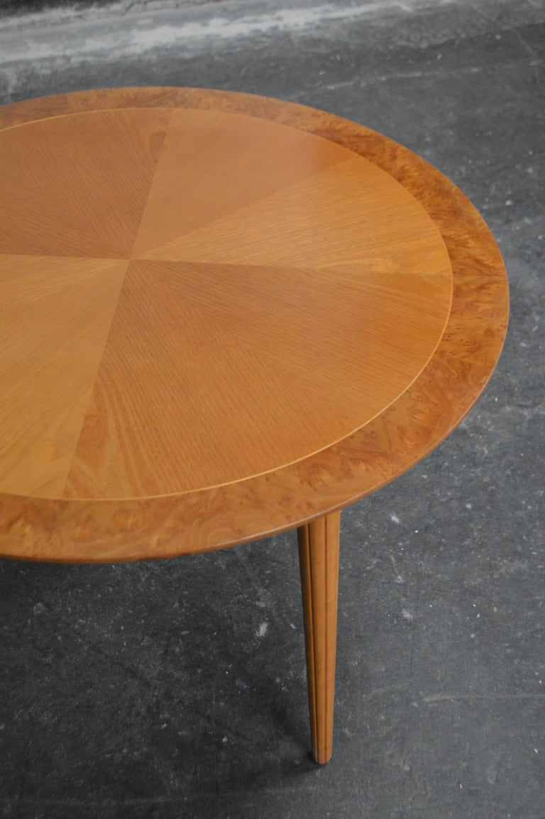 Swedish round golden elm end or side stable. Beautifully detailed with book matched top banded with Carpathian elm for additional interest. Atop tapered reeded legs. A very handsome table and perfectly scaled for any room. Legs can be cut down if