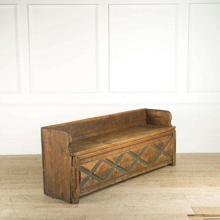 A rustic Folk Art bench (FÃ¥llbÃ_nk) from Dalarna. The FÃ¥llbÃ_nk or bench has a foldable seat and offers plenty of storage underneath.