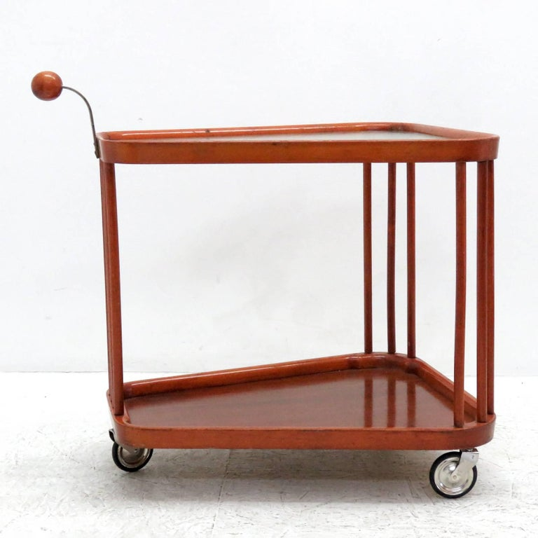 Sculptural two-tier wooden serving cart with textured glass top on three metal casters from Sweden, 1960s, with wooden spherical handle.