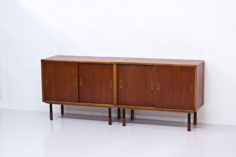 Pair of sideboards by Westbergs Möblers, manufactured in Sweden during the 1950s. Made from teak and oak, black lacquered legs with teak feet.  Drawers and shelves inside.