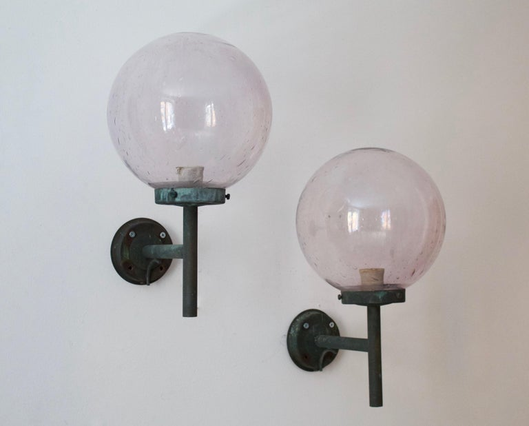A pair of sizable wall lights. Designed and produced in Sweden, 1950s. Features patinated copper and blown glass shades with a light purple tint.