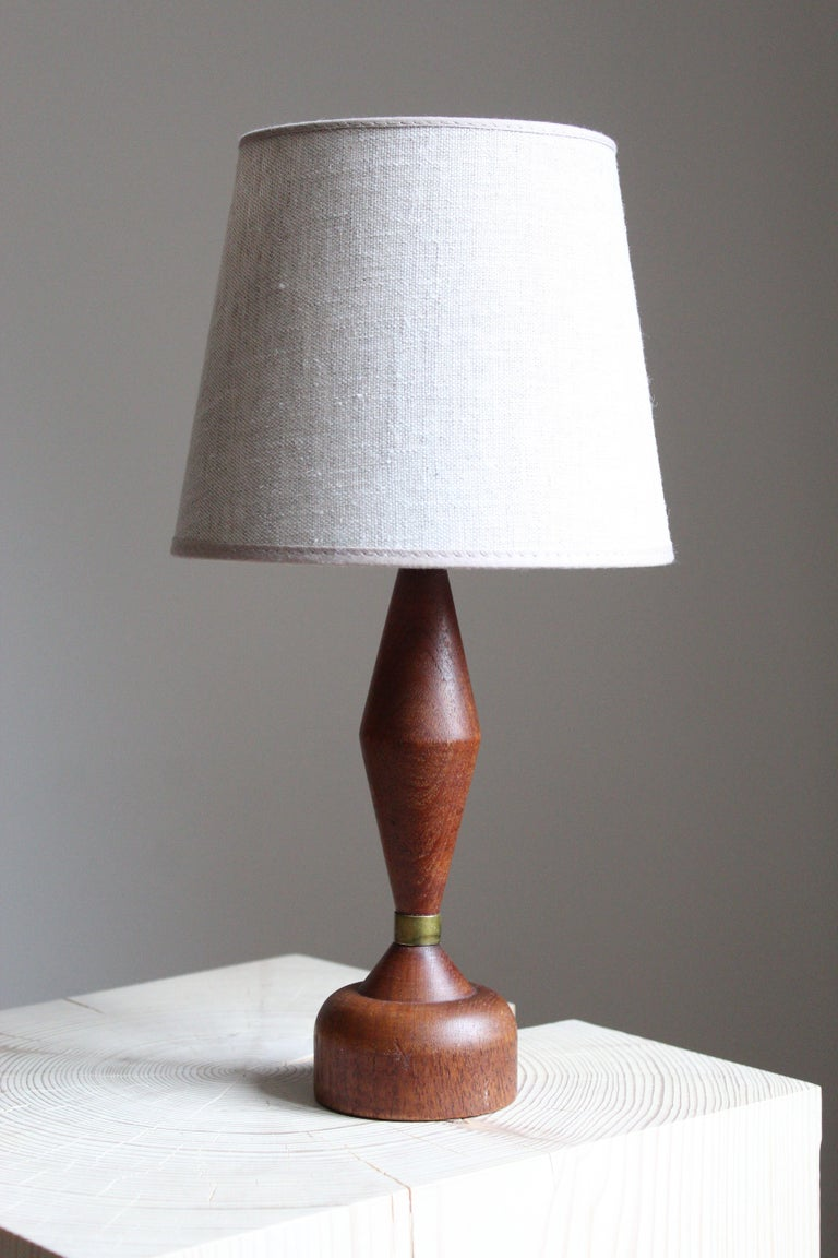 A small table lamp. In solid teak, with brass detailing. Brand new linen lampshade. Produced in Sweden, 1960s.