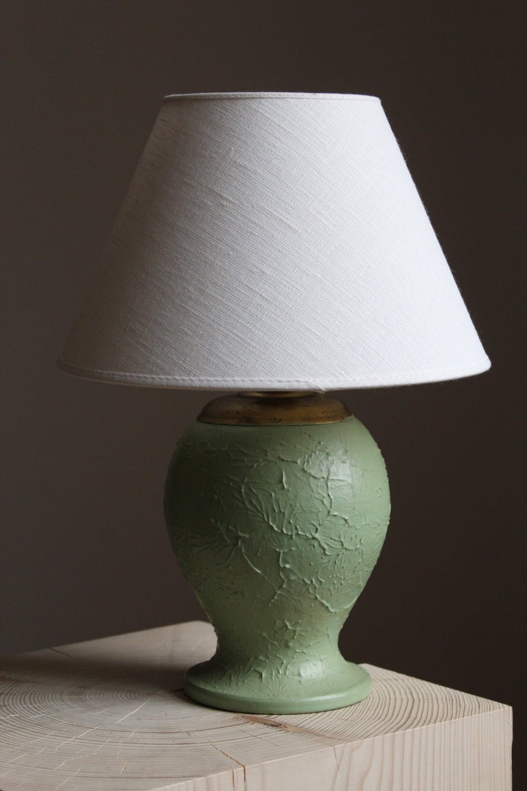 A table lamp, designed and produced in Sweden, 1930s. Base in light porcelein or eartherware. Brass details. Brand new high-end lampshade in linen.