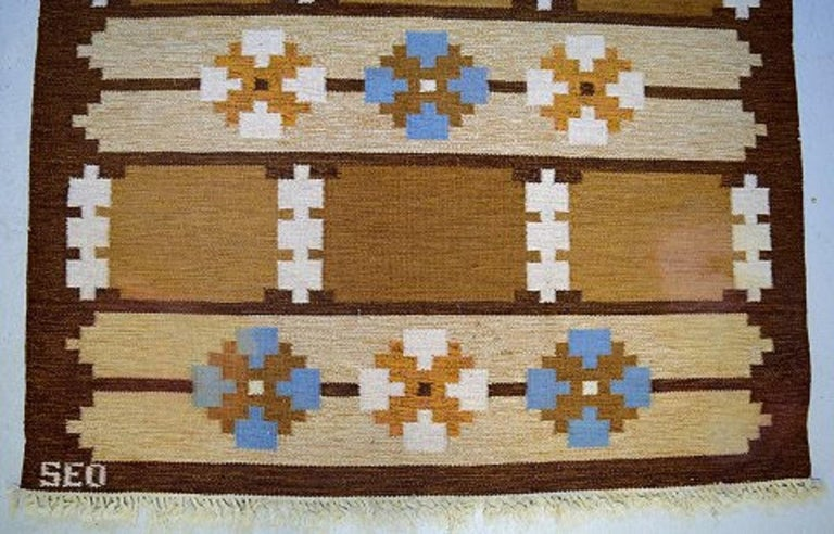 Swedish textile designer.  Large handwoven Rölakan rug in pure wool with geometric fields and clean lines in brown, blue and sand-colored shades, mid-20th century. Measures: 230 x 165 cm. In excellent condition. Signed in monogram.