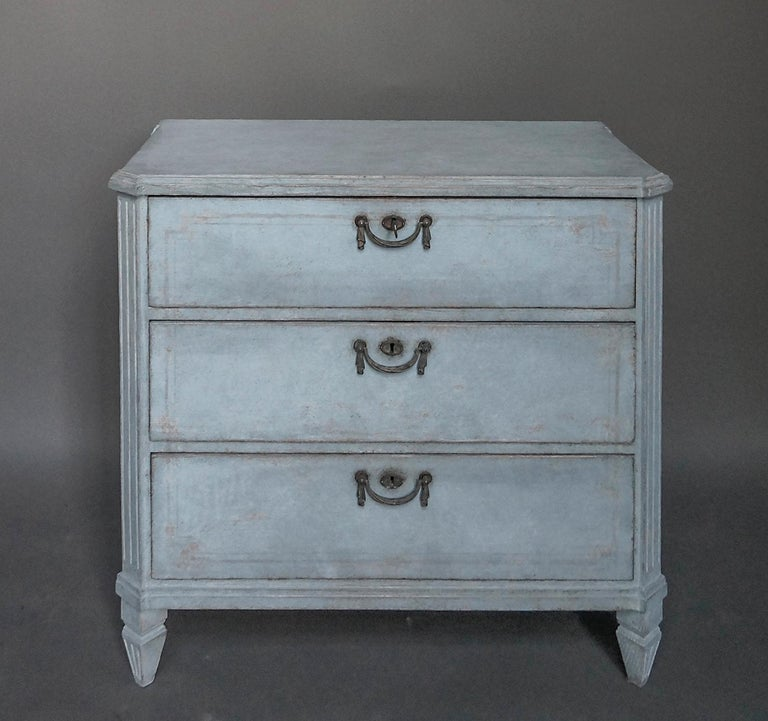 Nice little three-drawer commode in soft blue paint, Sweden, circa 1880. Shaped top with canted corners, incised decoration on the drawer fronts, and period brass hardware.