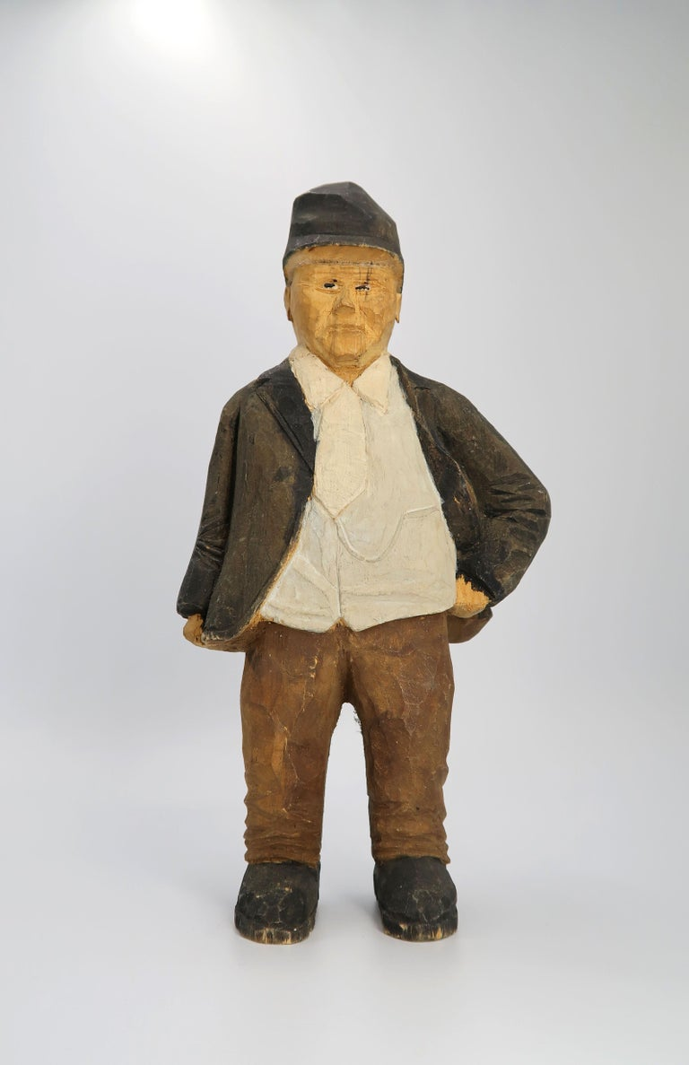 Unique and rustic Swedish midcentury wooden decorative sculpture depicting an older man in a traditional Swedish outfit for that time. He stands leaning on one leg with a hand in one side as if waiting, and wears a white shirt, dark jacket, brown