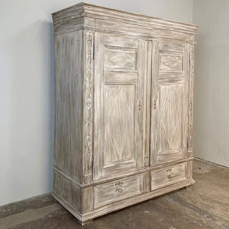 19th century Swedish whitewashed Armoire was handcrafted from solid oak, and features a unique combination of style renderings, from the distinctive dentil molding on the crown to the intaglio style carved cornerposts, and the tailored molding on
