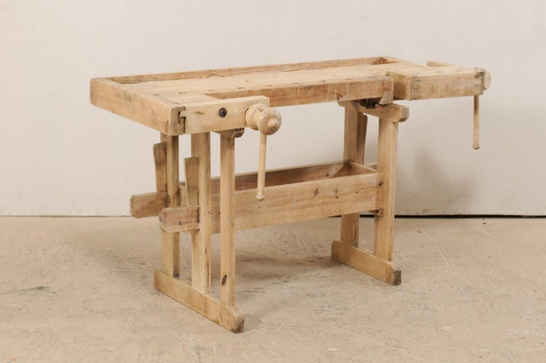 A Swedish work shop bench with clamps. This vintage work-bench from Sweden has a nice shallow profile with an overall rectangular-shaped top with recessed area and adjustable clamping mechanisms on two sides. The top is raised upon trestle style