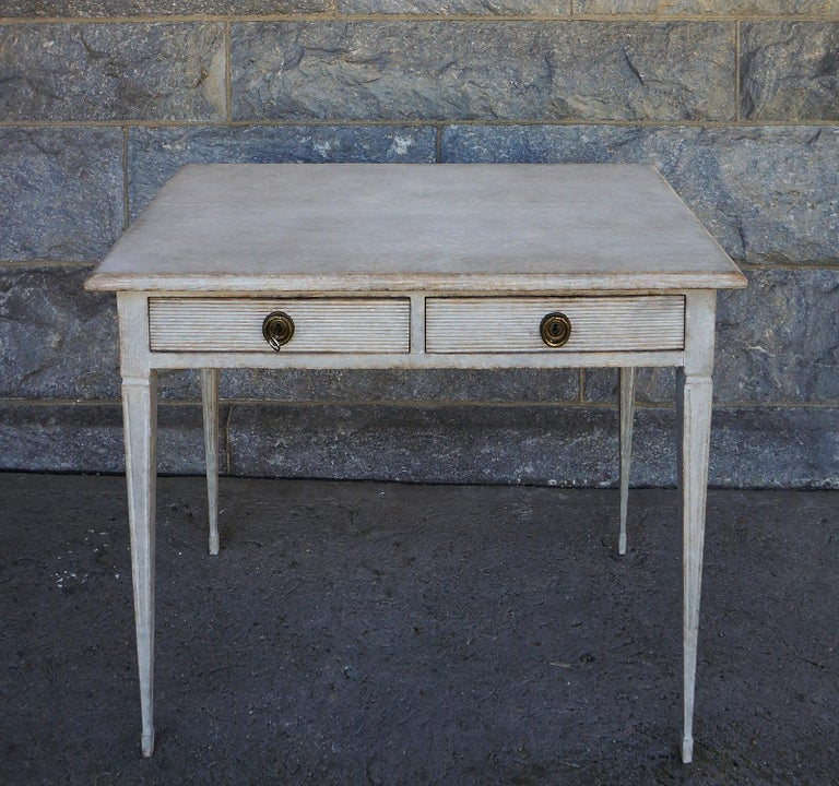 Gustavian style writing table, Sweden circa 1880, with two reeded apron drawers and tapering square legs with delicate spade feet. Brass pulls with integrated locks. Its finished back allows it to be used in a free-standing position.