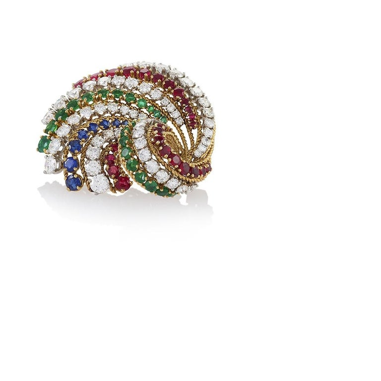 A French 18 karat gold brooch with diamonds, rubies, emeralds and sapphires by Van Cleef & Arpels. The sweeping brooch features 56 stunning F/G color and VVS/VS clarity diamonds graduating from .02 carat to .60 carat, with an approximate total