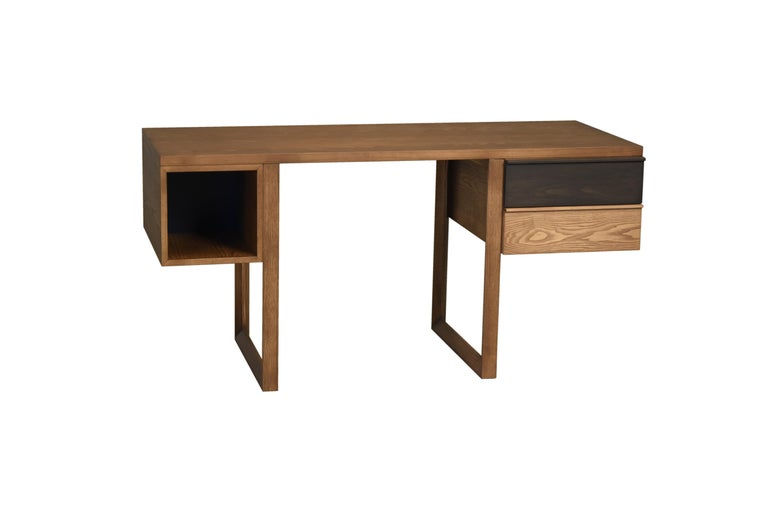 Writing desk made of ashwood with one open element and two drawers available in different finishes.