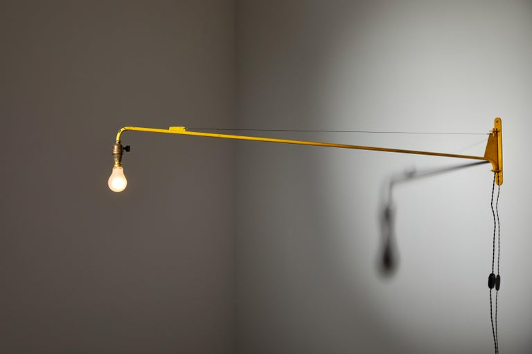 Swing Jib wall light by Jean Prouvé. Manufactured by Les Ateliers Jean Prouvé, France, circa 1950s. Original painted metal. Rewired for U.S. standards with black french twist silk cord. We recommend one 40w maximum bayonette bulb. Bulb provided as a