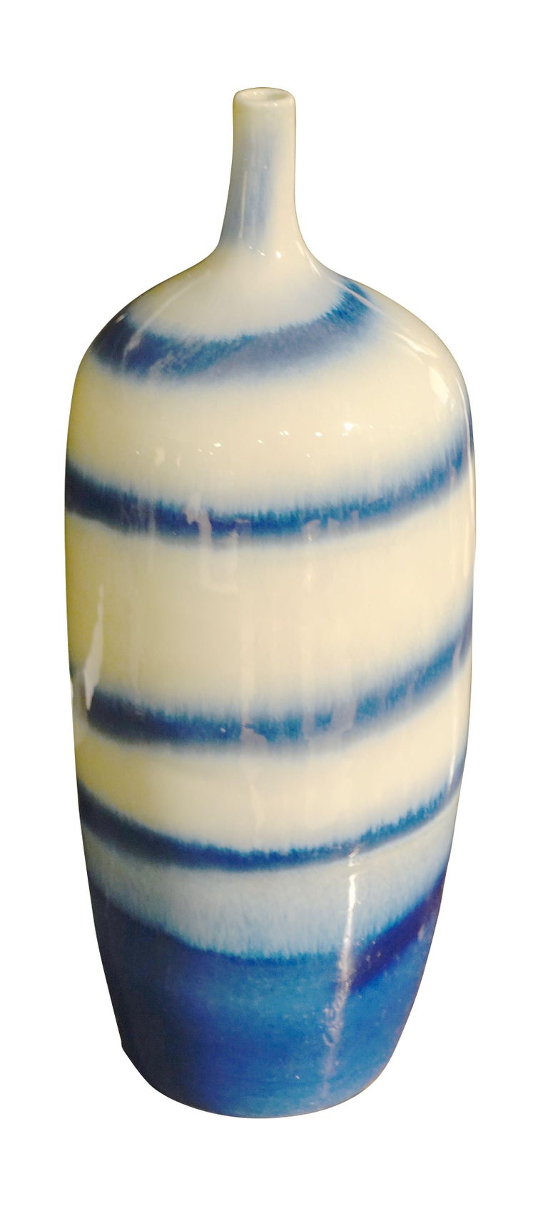 Contemporary Chinese shades of blue and white swirl pattern thin neck vase. Two are available and sold individually.