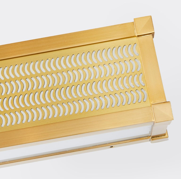 A rectangular, horizontal box-shaped light fixture. The brass frame engraved with comma shaped cut outs which emit light. Panels feature bevelled corner details, while the front sides and underside are fitted with opal plexi diffusers.  As part