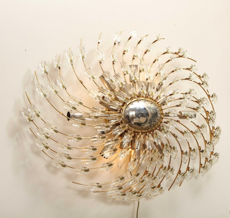 Swirling Italian glass wall light fixture in polished brass. A unique fixture with a small oval mirror and hexagon glass pieces in a swirling manner. There are 16 sockets total. Overall wear is consistent with age and use. Few glass pieces are