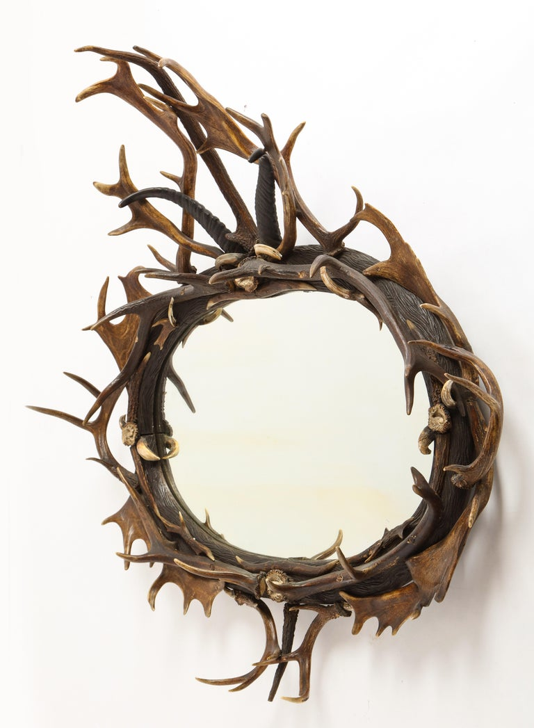 A Swiss 'Black Forest' antler and boar tusk-mounted cartouche-form wall mirror mounted with a carved linden wood frame carved with hatch marks and adorned with a symmetrical application of Roe buck antlers with interspersed boar tusks. A central
