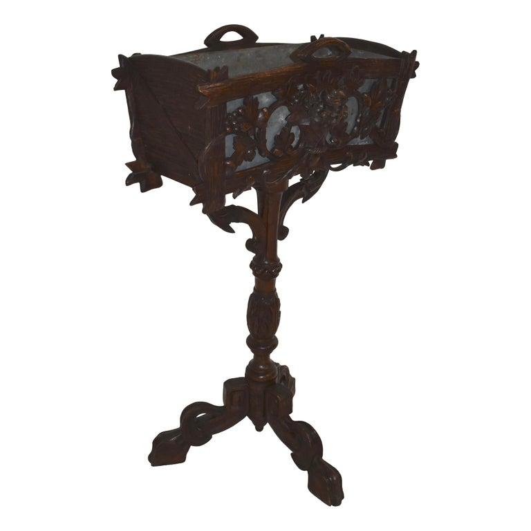 Graceful and elegant, this beautiful wooden planter box features a pierced front carving of a floral basket flanked by scrolled grape vines. The back and sides of the box are carved to look like rough wooden boards. Raised on a turned and carved