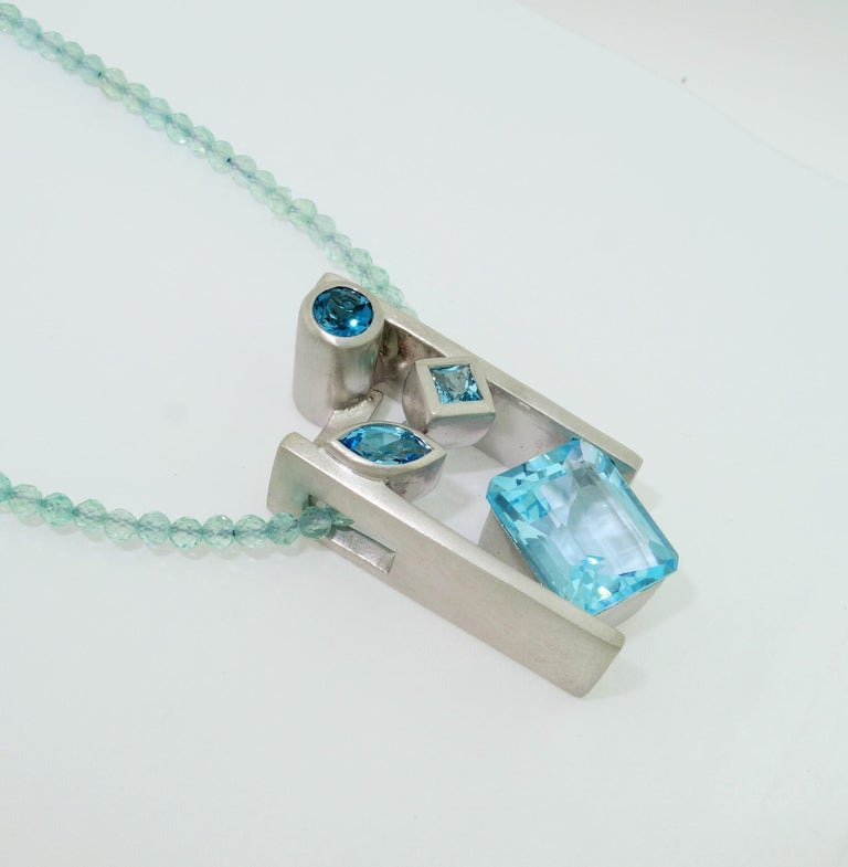 Beautiful and finely detailed Swiss Blue, London Blue and Sky Blue Topaz Pendant set in Sterling Silver and suspended from a Blue Apatite Necklace; approx. total weight of Topaz: 6.33 Carat; The pendant is Hand crafted in Rhodium Sterling Silver and