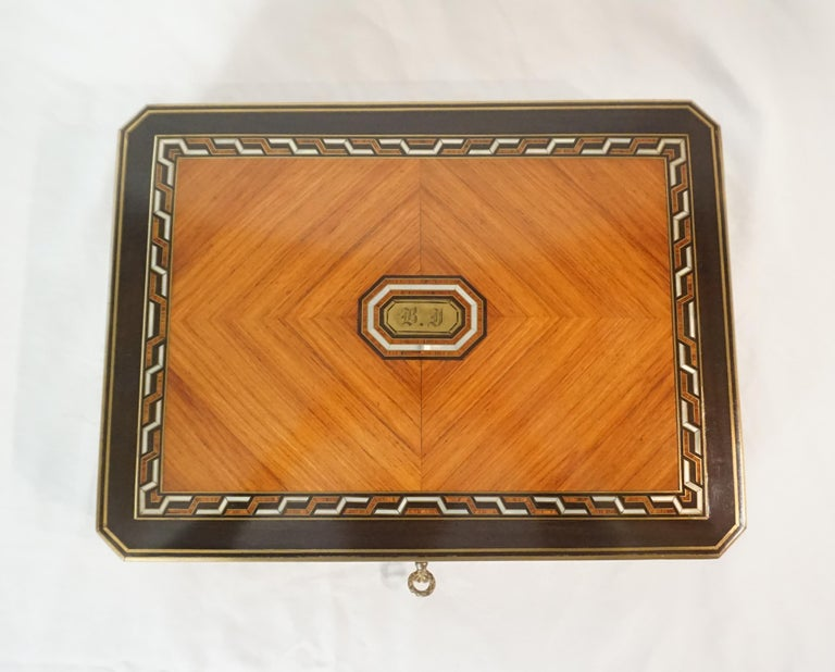 An exquisite Swiss, circa 1890, exotic-woods games box of rectangular form with canted edges; the slightly domed top with brass and ebony inlaid perimeters surrounding geometric nacre (mother-of-pearl), ebony, and brass inlaid border framing