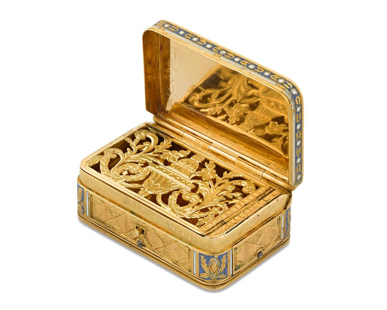 A musical movement distinguishes this wonderful early 19th-century gold vinaigrette box. The vessel is covered in delicate engraving highlighted by blue and white champlevé enamel detailed in a fine floral motif. The button on the front of the box