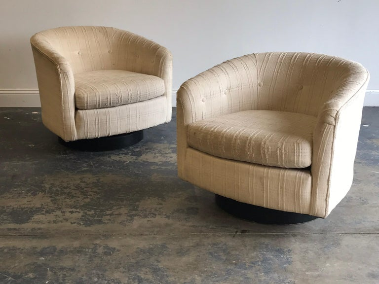 Iconic pair of swivel tub chairs attributed to Milo Baughman. Ebonized wood base supports a tub shaped swivel chair. Swivel mechanism works well. Present tag appears to be from an upholstery shop. New upholstery recommended.