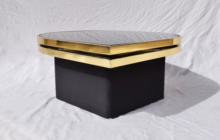 Elegant reverse black painted glass and brass cocktail or coffee table with floating upholstered base designed and manufactured by Richard Barry for Design Institute of America (DIA). The top of two striking teardrop surfaces swivels smoothly
