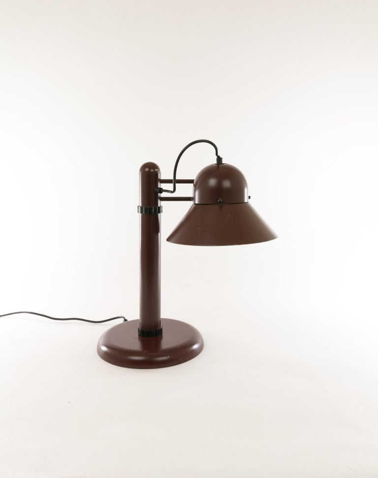 Swiveling dark brown table lamp of lacquered metal designed by Gae Aulenti and manufactured by Stilnovo in the 1970s.  This model had been produced for all possible different applications. The floor lamp and the ceiling lamp for instance have been