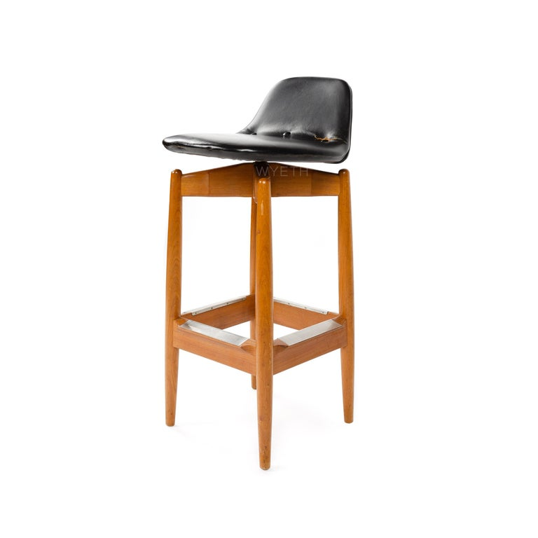 A teak barstool with a leather swivel seat.