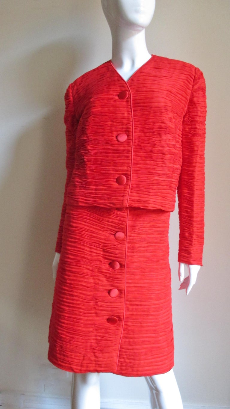 An incredible red suit in delicately pleated fine linen made famous by Sybil Connolly. The jacket closes in front with matching buttons and bound buttonholes and is piped around the V neckline and along the center front. The A line button front