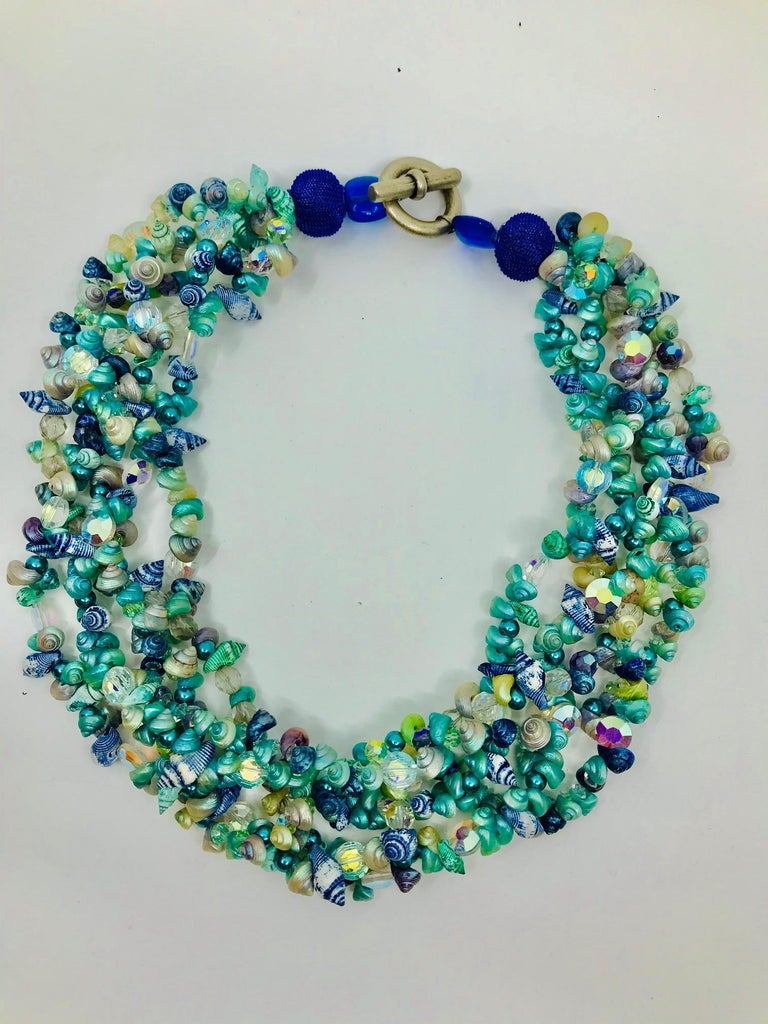 This statement  necklace consists of 5 strands of tiny shells and Swarovski beads ,finished by larger blue beads and silvered clasp. Tiny shells are rom Tasmania . In the past they were collected by Aboriginal women for their daughters wedding