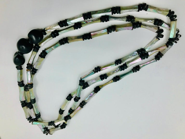 Long 3 strand Necklace with  up-cycled turquoise Art Deco Abalone beads. The beads are exquisitely hand crafted from thin Abalone /Haliotis hand cut pieces with black bone ends.The long Necklace spacers are  small wooden beads . As an accent it has